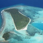 Atoll with wave facing reef in front of a vegetated carbonate sand cay and protected lagoon